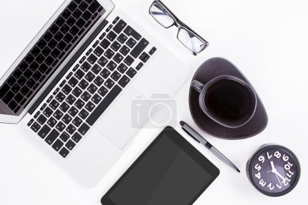 Photo for Top view of white office desktop with blank tablet, laptop, pen, clock, coffee cup and glasses. Mock up - Royalty Free Image