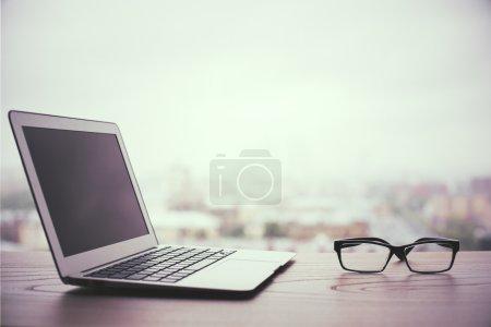 Blank laptop on city background