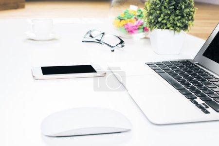 Photo pour Gros plan de bureau blanc avec blanc smartphone, clavier d'ordinateur portable, souris d'ordinateur, verres, tasse à café et objets décoratifs. Maquette - image libre de droit