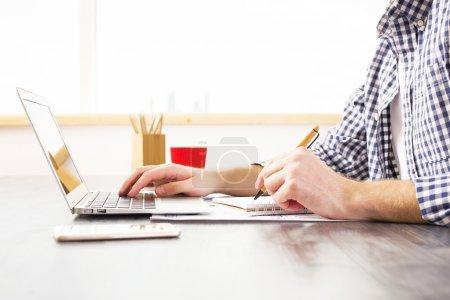 Photo pour Vue latérale du jeune homme d'affaires au bureau en utilisant un ordinateur portable et un bloc-notes pour travailler sur le projet - image libre de droit