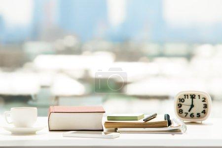 Photo pour Gros plan de bureau blanc avec tasse à café, livre fermé, smartphone, articles de papeterie et horloge sur fond de ville flou avec la lumière du soleil - image libre de droit
