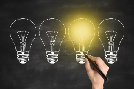 Photo for Idea concept with businessman's hand drawing abstract illuminated light bulbs on chalkboard background - Royalty Free Image