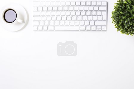 Photo for Top view of white office desktop with keyboard, coffee cup, plant and copy space. Mock up - Royalty Free Image