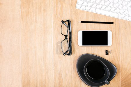 Photo for Top view of wooden office desktop with blank smartphone, coffee cup, spectacles, supplies and keyboard. Mock up - Royalty Free Image