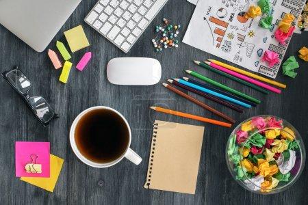 Photo pour Vue du dessus de bureau désordonné avec feuille de papier brun vierge, tasse à café / thé, lunettes, clavier, ordinateur portable fermé, croquis d'affaires et fournitures colorées. Maquette - image libre de droit