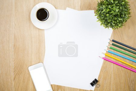 Foto de Vista superior de la hoja de papel en blanco, teléfono inteligente blanco, taza de café, planta decorativa y otros suministros en escritorio de madera. Prepárate. - Imagen libre de derechos