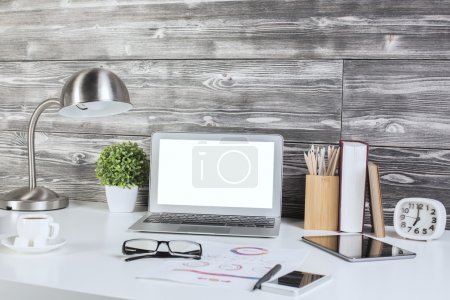 Photo for Creative office desktop with blank white laptop screen, lamp,glasses, smart phone. Mock up - Royalty Free Image