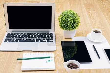 Photo for Front view and closeup of creative designer workplace with blank laptop, decorative plant, spiral notepad, coffee cups, tablet, smartphone and other items. Mock up - Royalty Free Image