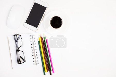 Photo pour Vue du dessus et gros plan du bureau blanc avec téléphone cellulaire vierge, souris d'ordinateur, bloc-notes en spirale, lunettes, crayons colorés et tasse à café. Maquette - image libre de droit