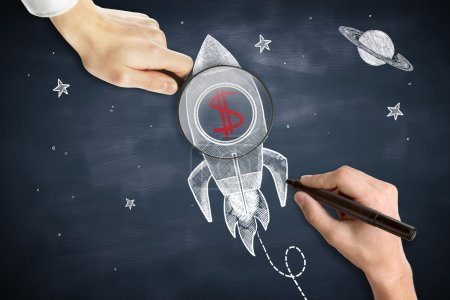Male hands drawing and holding magnifier over space ship sketh with red dollar sign. Chalkboard background. Start up concept