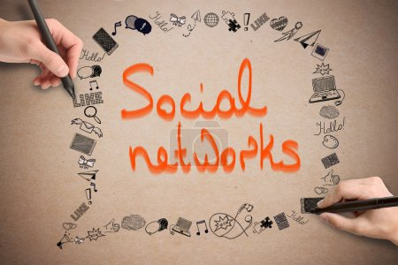 Hands drawing media related doodles on cardboard background with orange text. Social networking concept