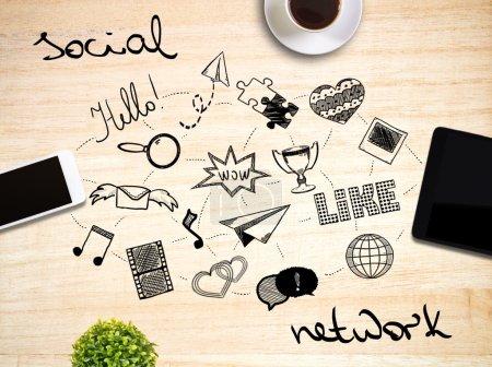 Photo pour Vue du dessus de bureau en bois clair avec téléphone portable, pad, tasse à café, plantes et gribouillis abstraits liés au réseau social - image libre de droit
