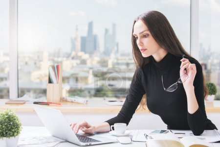 Photo for Portrait of beautiful caucasian business woman using laptop computer at office desk with coffee cup, paperwork and other items. City view in the background - Royalty Free Image