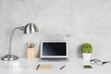 Photo for Creative designer desktop with blank laptop computer, smartphone, glasses, notepad, coffee cup, colorful pencils, plant and table lamp on concrete wall background. Mock up - Royalty Free Image