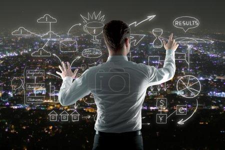 Photo pour Homme d'affaires gérant croquis abstrait d'affaires sur fond de ville de nuit - image libre de droit