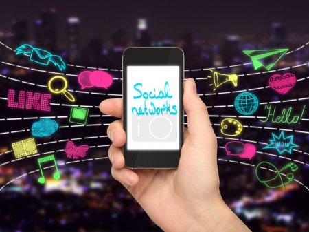 Photo for Hand holding smartphone with text on screen and colorful media icons on city background. Social networks concept - Royalty Free Image