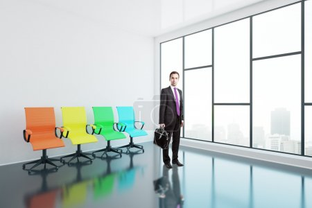 Businessman and colorful swivel-chairs