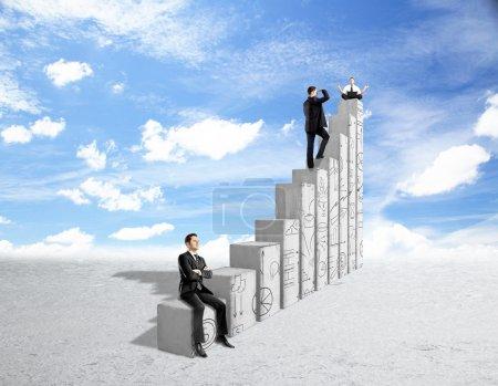 Photo pour Trois jeunes gens d'affaires debout, assis et méditant sur des barres graphiques abstraites en béton avec des gribouillis d'affaires sur fond de ciel. Concept de croissance financière et de réussite - image libre de droit