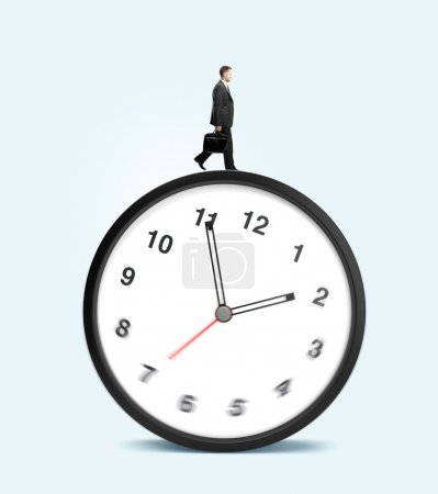 Photo for Man walking on clock on a blue background - Royalty Free Image
