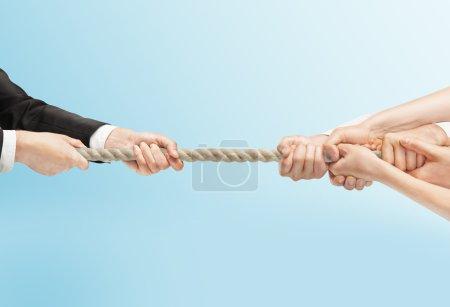 Photo pour Personnes tirant à la main la corde sur un fond bleu - image libre de droit