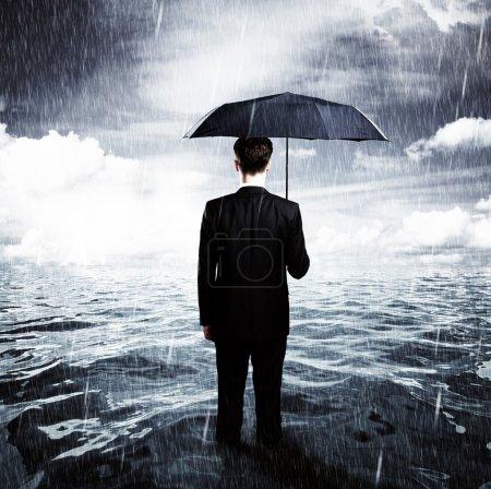 Photo pour Homme avec parapluie debout dans l'océan concept d'affaires - image libre de droit