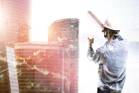 Photo pour Constructeur debout et pointant vers gratte-ciel - image libre de droit