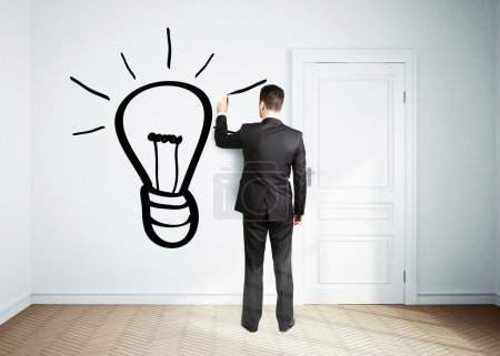 businessman drawing lamp