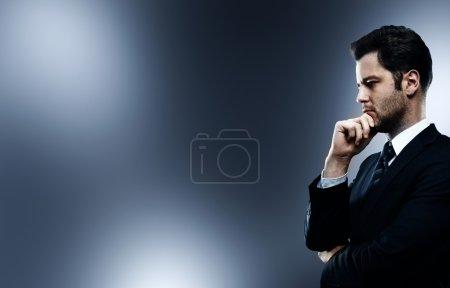 Foto de Hombre de negocios pensando en un fondo gris - Imagen libre de derechos