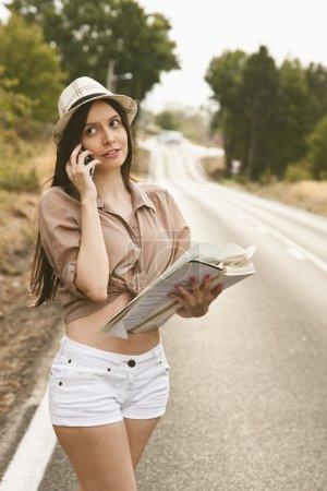 Photo pour Fille sur la route parler au téléphone - image libre de droit