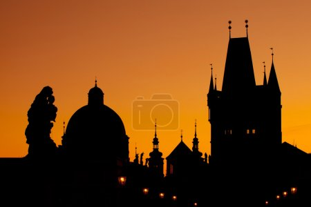 The silhouettes of towers and statues on Charles Bridge in Pragu