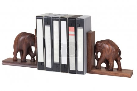 Elephant bookend with video cassette over white...