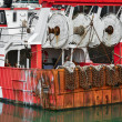 Red rusty boats and metal nets for catching scallo...