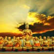 Golden buddha statue in buddhism temple thailand against dramatic sun rising with ray beam background