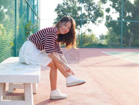 Photo pour Portrait de fille beau sport assis dans les courts de tennis à la recherche d'appareil photo avec sourire visage utilisation pour les personnes et les activités de mode de vie sain - image libre de droit