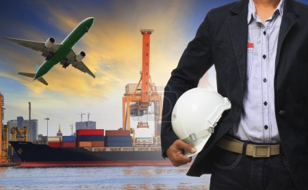 Photo for Manager man holding safety helmet standing against ship and container on shipping port and cargo plane flying above use for freight and logistic transport industry - Royalty Free Image