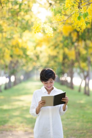 Photo for Portrait of young beautiful asian woman standing in yellow flowers blooming park summer season and reading a book with happy face emotion - Royalty Free Image