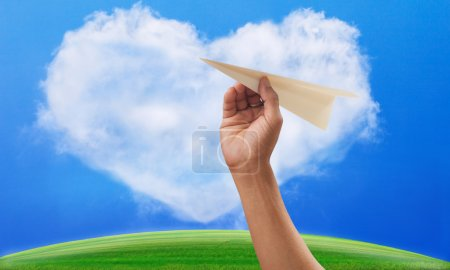 Hand preparing to throwing paper plane to mid air againt green g
