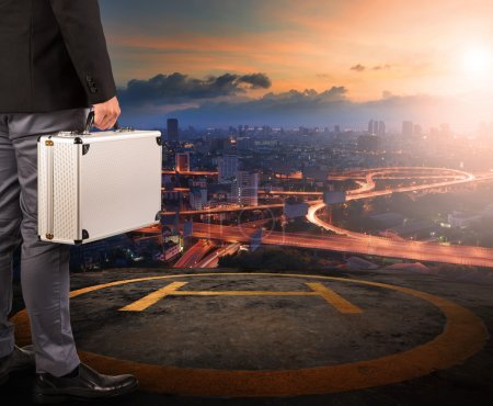 Photo for Business man with strong metal breifcase standing on helicopter pad on top of building roof with sun rising over urban scene - Royalty Free Image