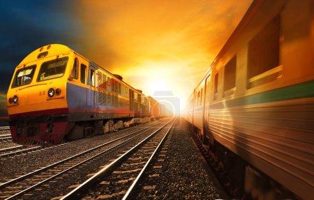 Photo pour Trains de voyageurs et de l'industrie des chemins de fer porte-conteneurs circulant sur la voie ferrée contre le beau soleil couché ciel utilisation pour le transport terrestre et les affaires logistiques - image libre de droit