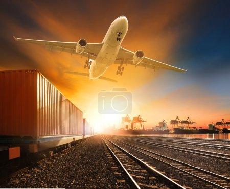 Photo pour Industrie conteneur tramway en cours d'exécution sur les chemins de fer piste avion cargo volant au-dessus et le transport de navires dans le chantier de conteneurs d'exportation d'importation - image libre de droit