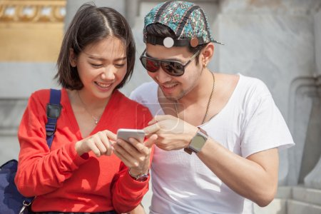 young man and woman looking to smart phone screen use for modern