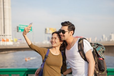 couples of younger man and woman take a selfie photograph by sma
