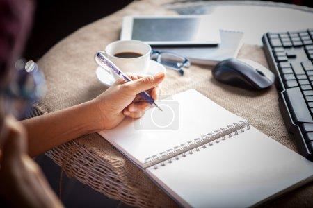 Photo pour Personnes qui prennent des téléphones mobiles et table top travaillant en écrivant sur la page de papier blanc de vide avec la main gauche - image libre de droit