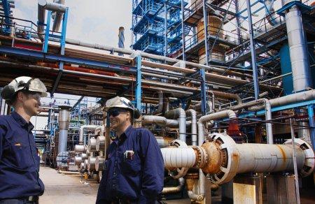 Photo pour Deux travailleurs du pétrole et du gaz à l'intérieur d'une grande raffinerie, pipelines et pompes - image libre de droit