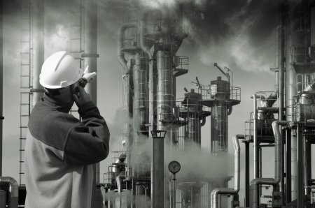 Photo for Oil and gas worker in hard-hat pointing at industrial refinery, smoke and smog - Royalty Free Image