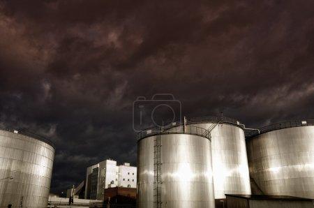 Photo pour Grands réservoirs industriels de carburant et d'huile, tournés au coucher du soleil avec du métal brillant - image libre de droit