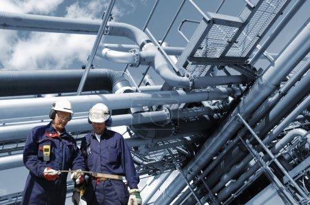 Photo pour Deux ouvriers de raffinerie, mécaniciens avec de grandes constructions de pipelines - image libre de droit