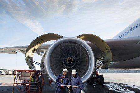 Photo pour Deux mécaniciens d'avion, ingénieurs devant un gros moteur jumbo-jet - image libre de droit