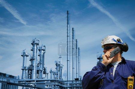 Photo pour Travailleur du pétrole et du gaz parlant au téléphone devant une grande raffinerie de pétrole et de gaz - image libre de droit