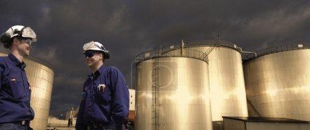 Photo pour Travailleurs du pétrole et du gaz, ingénieurs devant les réservoirs de stockage de carburant, coucher du soleil, début de soirée - image libre de droit
